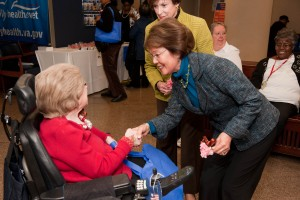 Two women shaking hands. One of them is in a wheelchair.