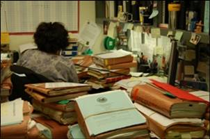 Claims processor at her desk surrounded by files