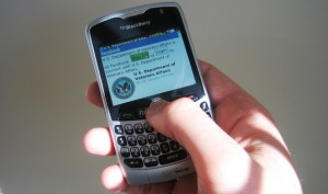 Person's hand holding a Blackberry set to VA's Facebook page