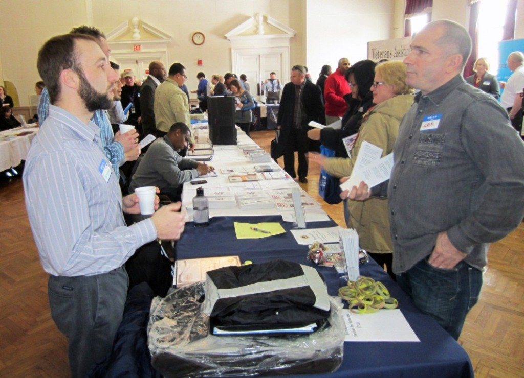 Jamison Hild, Case Manager for Supportive Services for Veterans and Families, left, talks to Cristofer Mishler, from Thresholds, during the resource fair at the Lovell Federal Health Care Center annual Homeless Veterans Summit 2014.