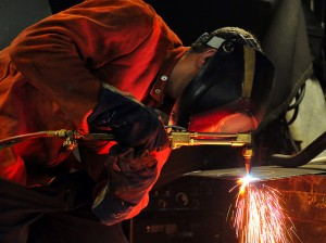 Hull Technician Fireman Tristan Reynolds arc-welds a flange aboard the amphibious dock landing ship USS Pearl Harbor