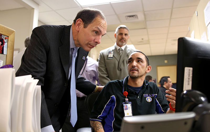 VA Secretary Bob McDonald learns more about VA's scheduling system from Michael Logie, Medical Support Assistant at the Phoenix VA Medical Center.