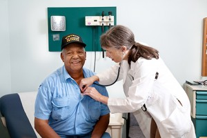Image of a Veteran getting a check up from a female VA doctor