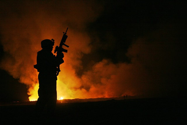 night image of a soldier silhouetted against a burnpit