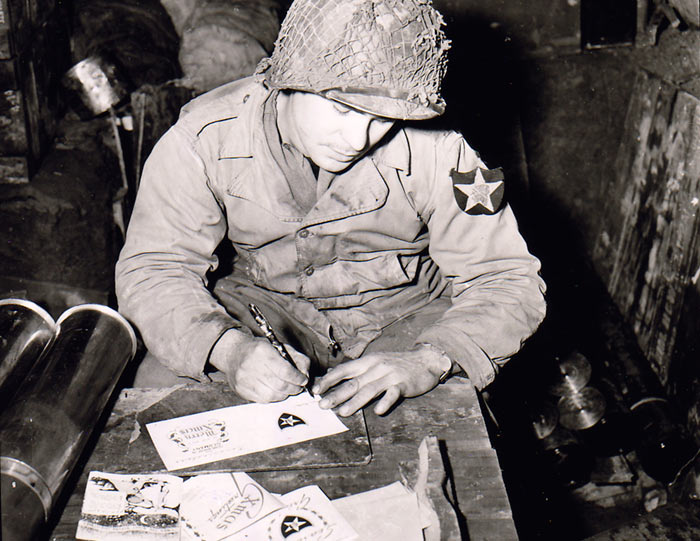 Seated at a box in a storehouse for artillery shells, in Germany, Pvt. Walter E. Prsybyla, member of the 2nd Infantry Division, addresses Christmas cards to the folks back home. 11/30/44. B Btry, 37th FA, 2nd Inf. Div., FUSA, Heckhalenfeld, Germany.