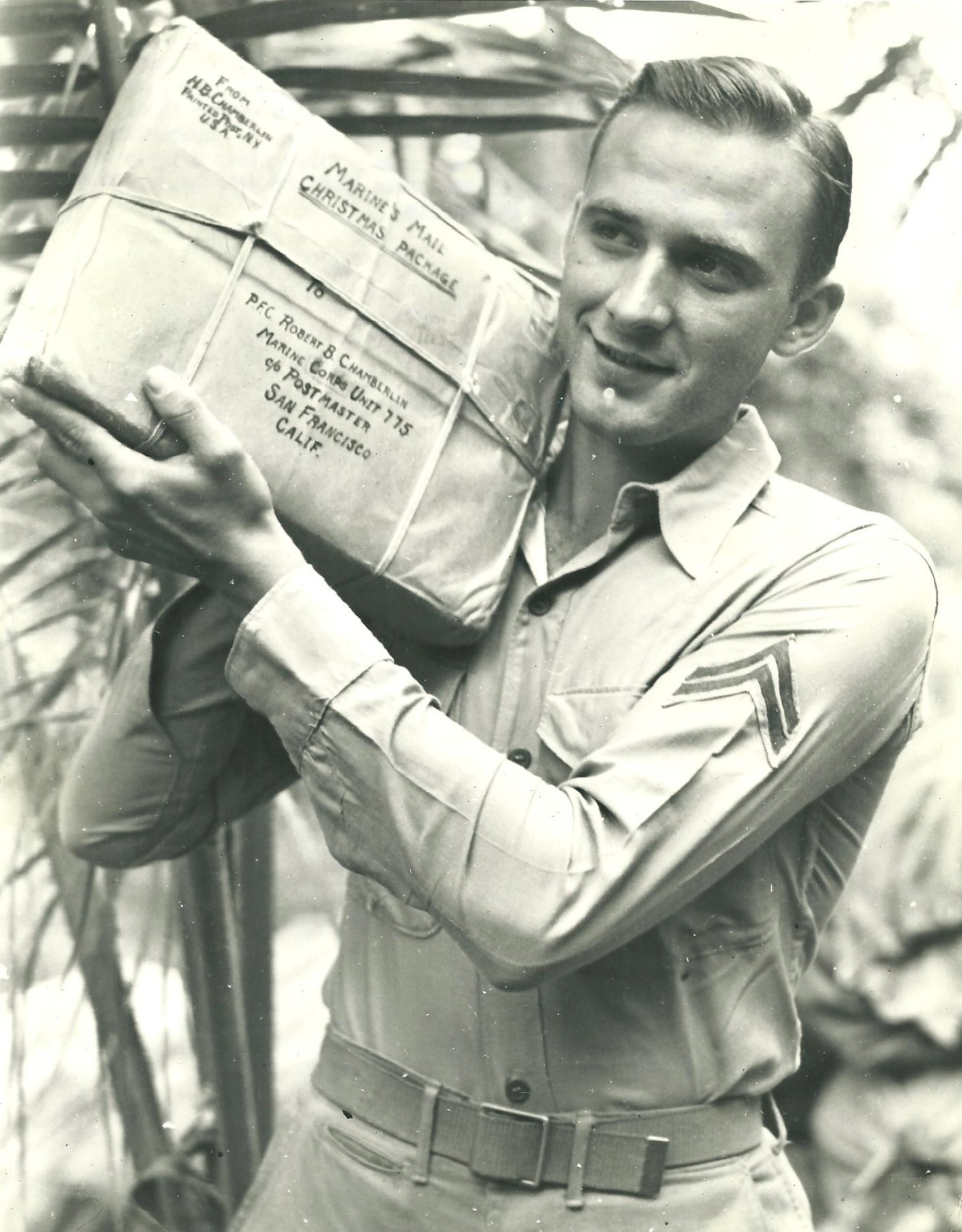 A Christmas package for happy Corporal Robert B. Chamberlin, member of a United States Marine Corps unit stationed in the southwestern Pacific. Christmas for this Marine Corps unit will lack the proverbial trimmings on this island of coconut palms and bananas, but packages and mail from home helped make up for that.