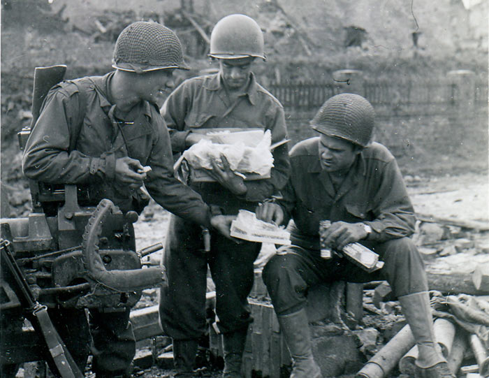 Pfc. Edmund Dill opens the Christmas package received from his wife. His buddies share the treat. Left, Pfc. Carl Anker; Right, Sergt. Ted Bailey. ETO, 11/18/44