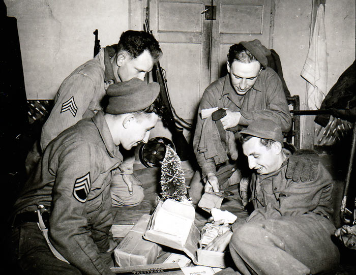 Sitting around a miniature Christmas tree and opening a Christmas package are (front row, left to right) S/Sgt. John F. Suchanek; and Pfc. Joseph G. Pierro; and (back row) Sgt. Charles M. Myrich; and Sgt. Leon L. Oben. All are members of F. A. Bn., 3rd Div. Pietramelara, Italy. December 16, 1943.