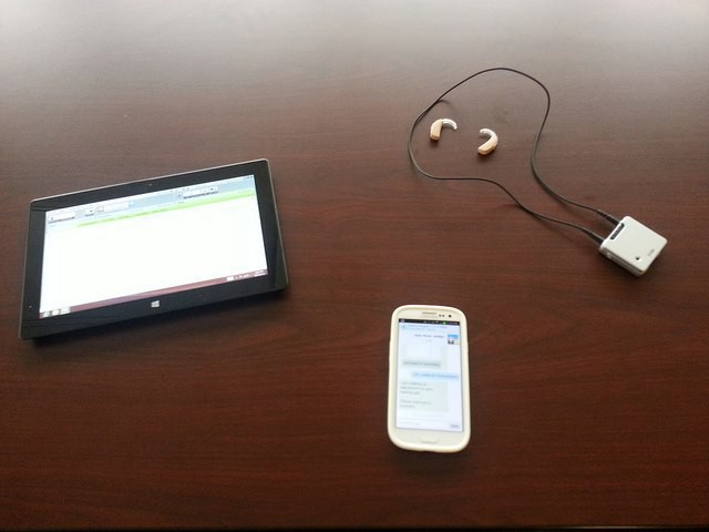 The technology on the patient's end: a tablet with installed software, smartphone with installed app, Phonak hearing aids, and iCube bluetooth device.