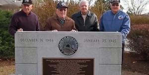 Battle of the Buldege Veterans standing infront of a sign.