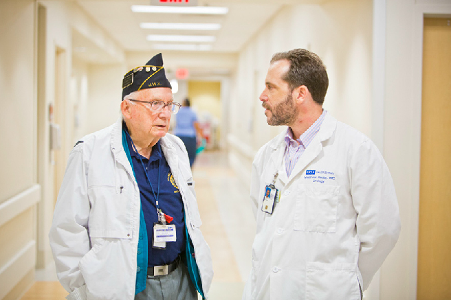 A doctor speaking to an older veterans in a VA hospital.