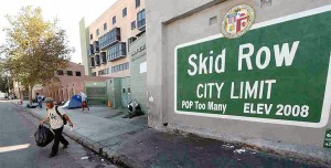 Sign on a wall in LA that reads Skid Row