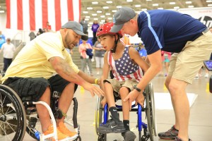 A Veteran helps a young athlete navigate the obstacle course.