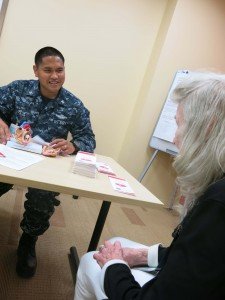 A man in Navy uniform sits at a table wth a woman
