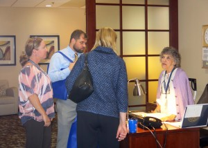 A group of people listen to a nurse talking at a desk.