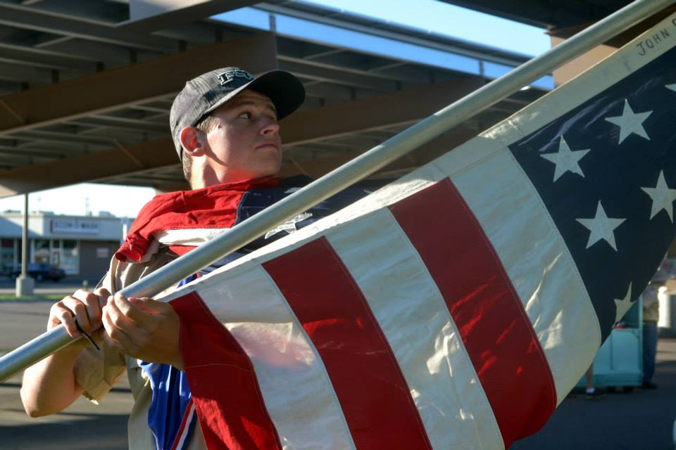 Boy Scout with one of 12 Forty eight star flags left at the Grand Junction VA