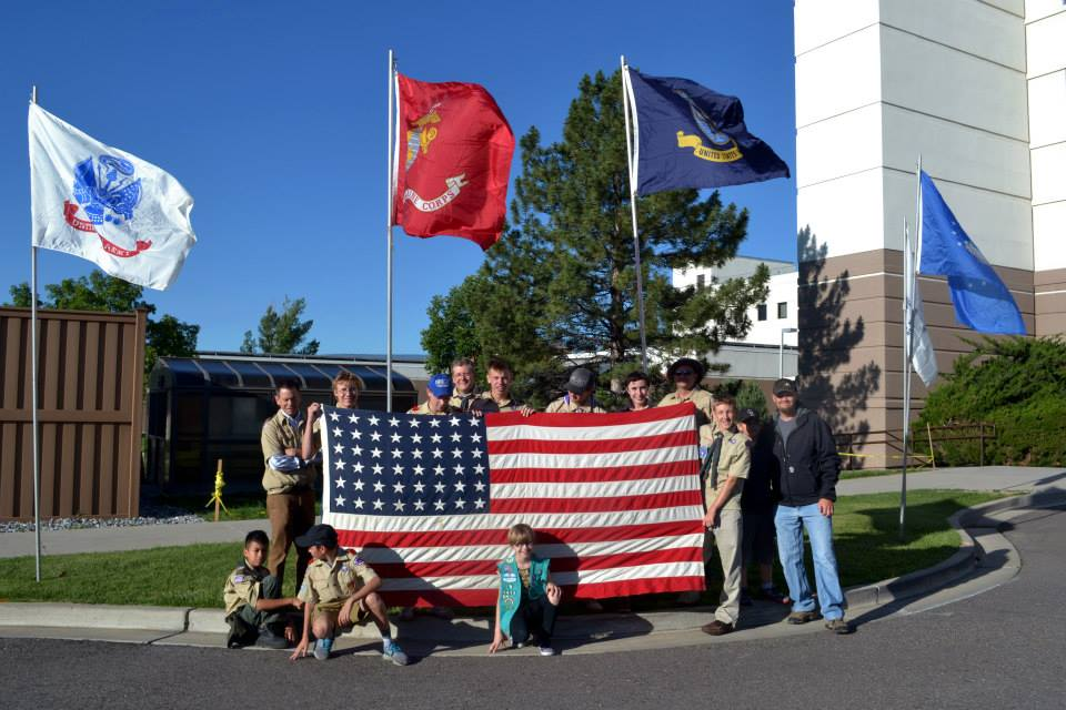Boy scouts stand around an American Flag in front of a VA Medical Center
