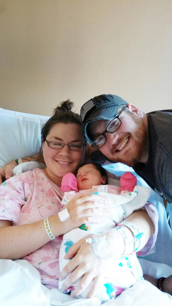 A man and woman with a new born baby.