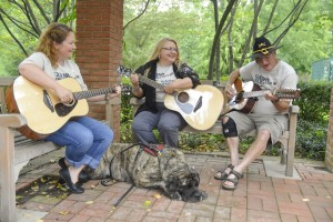 Two women and a man play guitars while a dog sits at their feet.