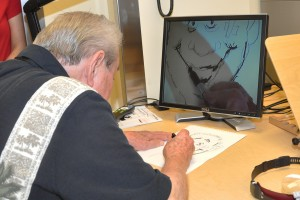 A man paints in front of a computer monitor.