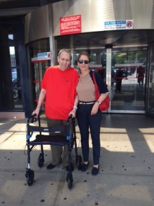 A man and woman stand outside some doors. The man has a walker.