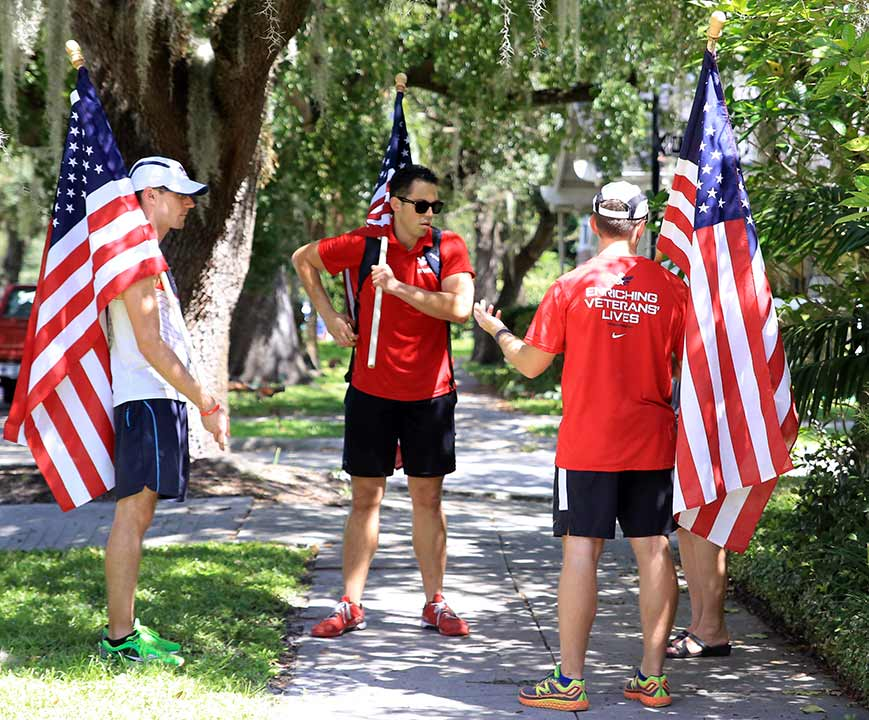 Drew Smith and other Team RWB members talk to a local resident about the 9/11 moving flag tribute.