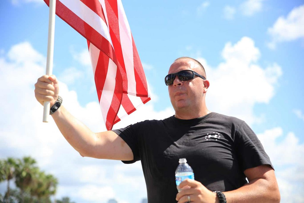 A Veteran participating in the 9/11 moving flag  tribute carries the flag on Bayshore Drive in Tampa, Florida