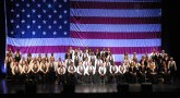 A choir sits in front of the American flag