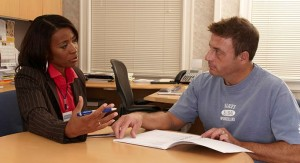 A woman talks with a man at a table.