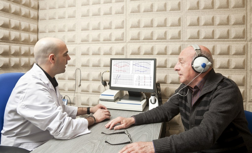 A docotro sits with a man in headphones