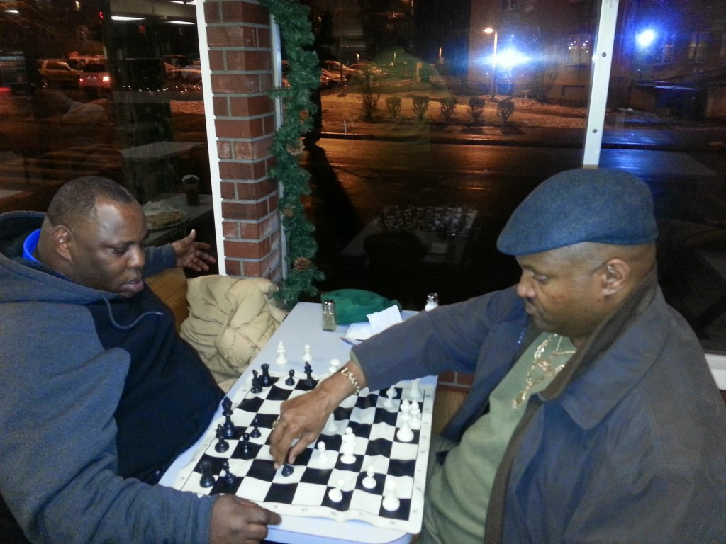 Two men play chess inside.