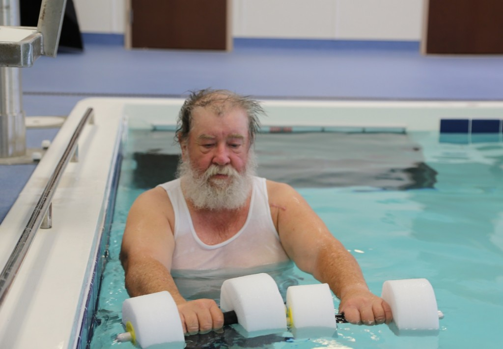 A man holds two water weights in a pool.