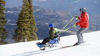 Two people ski, one in a seated skier