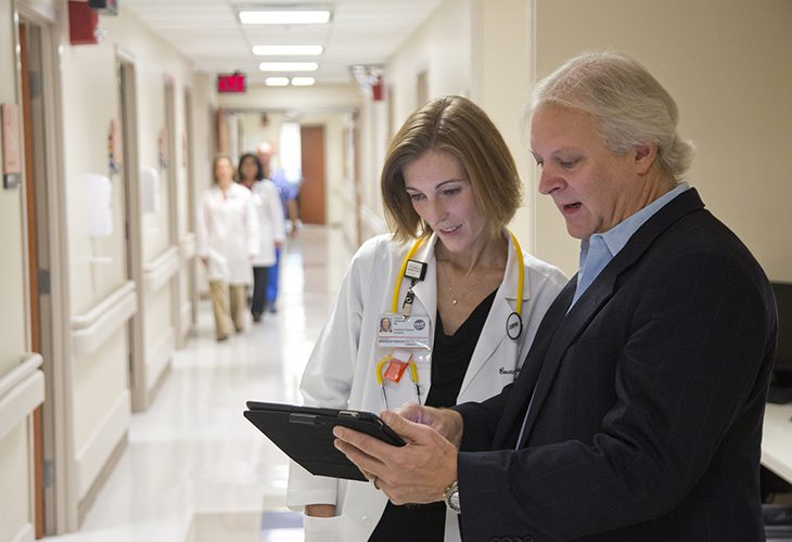 Image of a Female doctor and man in a suit reviewing medical chart in cancer hospital