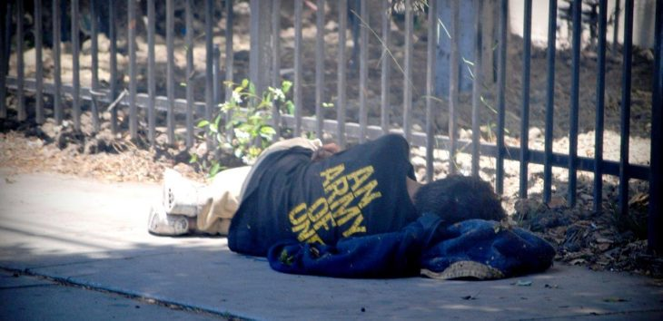 Image of a homeless man sleeping on the street.