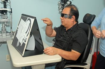 A man wears glasses and points at a board.