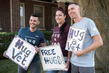 Three Veterans Posing with 'Hug a Vet' Sign
