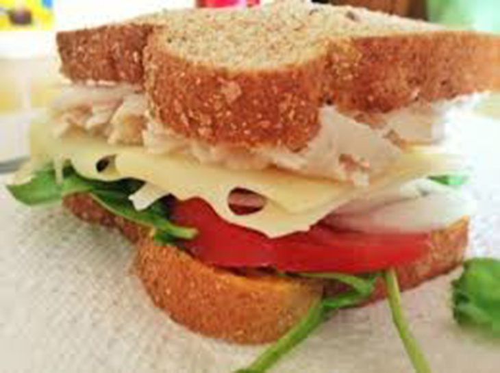 image of a sandich with swiss cheese, lettuce and tomato.