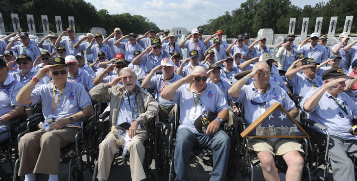 """Honor Flights to Washington, D.C.'s war memorials increased significantly after Labor Day, as D.C.'s fabled heat (theoretically) transitions to a more favorable fall climate. Groups from Arizona, Florida, Idaho and Chicago were some of the first to arrive in the nation's capitol Sept. 7 after the federal holiday.  Honor Flight Chicago celebrated its 74th flight since its inception, with 108 participants including 18 World War II and 90 Korean War Vets, in addition to the required support staff of more than 125 dedicated volunteers. Their day began much earlier than the 6:45 a.m. flight from Midway Airport-Chicago, to Dulles, Va.  They boarded buses and drove to the Iwo Jima Memorial where they were met by police motorcycle escort which guided them first to the Air Force Memorial for a performance by the Air Force Drill Team, before crossing the Potomac to the National World War II Memorial.  The group toured the memorial until a color guard honored the Veterans with pomp and circumstance. Center of the group, Arthur Kapinus, 89, a WWII Navy Veteran, held the flag-case filled with veterans portraits dear to members of the Honor Flight Chicago family.   Art was accompanied to D.C. by his brother Bernie, an 81-year-old Army Vet who served in Korea during the mid-50's. All told, eight Kapinus brothers have served in the military, mostly in the Army and Navy, since World War II. Their brother Joe, whose picture joined five others in the case, served with General Patton and was killed in Luxembourg in January 1945, at age 29.  John Ptak, president of Honor Flight Chicago is not a Veteran, but he has accompanied these flights since 2011, this his 20th trip.  """"This is my grandfather, he was in the army in WWII. He passed about 20 years ago, so he didn't get his Honor Flight,"""" you can hear emotion in his voice, as he gingerly touches the photo strung round his neck.  """"I didn't get a chance to take my grandfather, so I take other people's grandfathers"""".  S"""