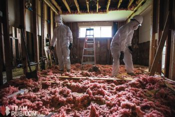 image of two people in hazmat suits removing insulation from a home