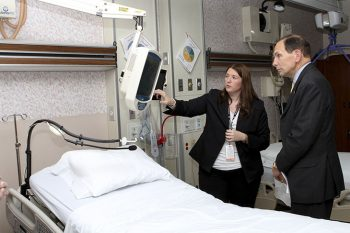 Image ofBob McDonald observing assistive technology in a hospital room.