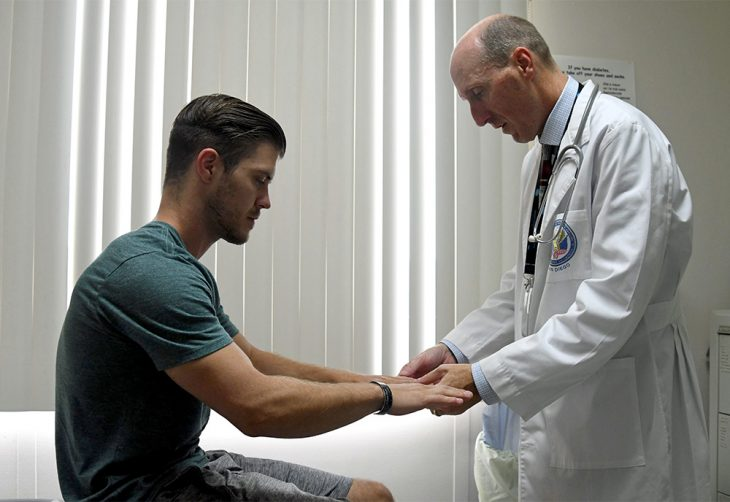 Doctor holds hands of patient.