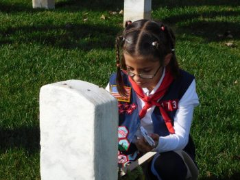 girl scout kneeling before a grave marker at Richmond National Cemetery, veterans legacy
