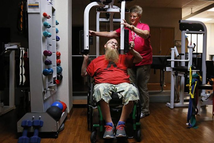 Tammy Beeler, a registered Kinesiotherapist, assists Emmet Pryor at the Dallas VA Medical Center Spinal Cord Injury Center train for the National Veterans Wheelchair Games.