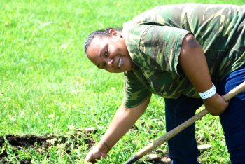 A woman bends over gardening.