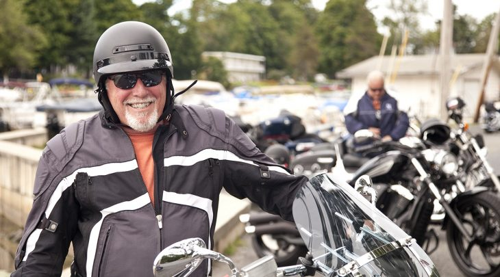 Motorcyclist smiling standing next to motorcycle on a cool riding day. Dressed in a warm jacket and helmet wearing sun glasses and parked in front of other motorcycles with unidentifiable biker behind him. Photo taken with Canon 5D Mark2 at 100 ISO, 24-115mm lens.