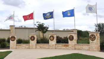 picture of entrance to Fort Same Houston National Cemetery, resting place of Carlos G. Martinez--flagfs of armed services flying over entrance