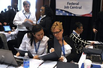 Image of two women engaged in a conversation at a both during a career fair.