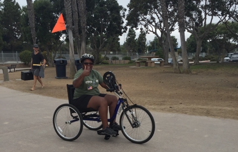 Harris tests an adaptive bicycle at the Summer Sports Clinic