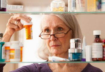 Female checking her medication for expired medicine for National Prescription Drug Day